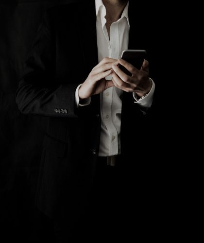 low-light-well-dressed-person-using-technology-pho-9PH8SLD